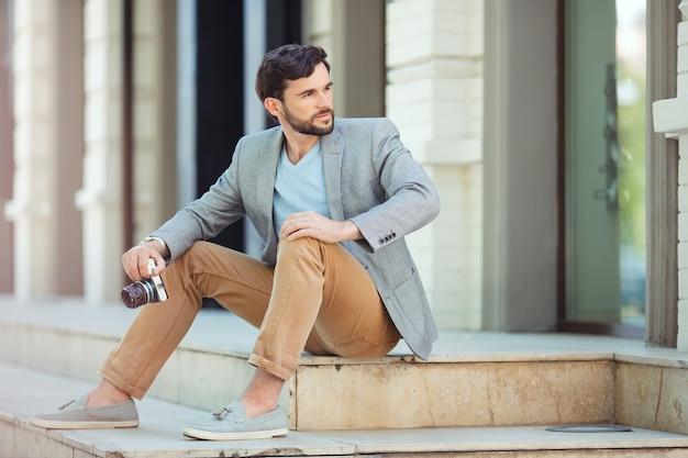 Männliche fotografenfront sitzt auf stufen draußen am nahen gebäude