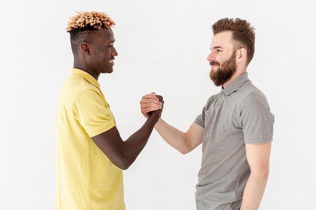 Männliche freunde der vorderansicht, die hände rütteln