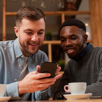 Männliche freunde des smiley, die auf mobile schauen