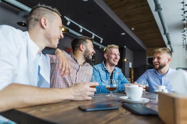 Männliche freunde, die am restaurant sitzen