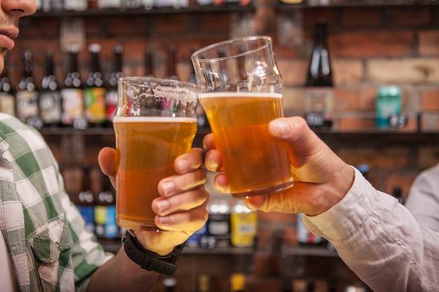 Männliche freunde, die biergläser an der kneipe klirren