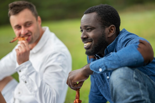 Männliche freunde, die draußen grill essen