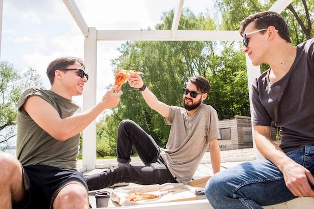 Männliche freunde, die pizza teilen