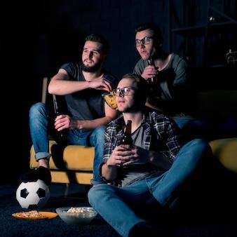 Männliche freunde, die zusammen sport im fernsehen schauen, während sie snacks und bier haben