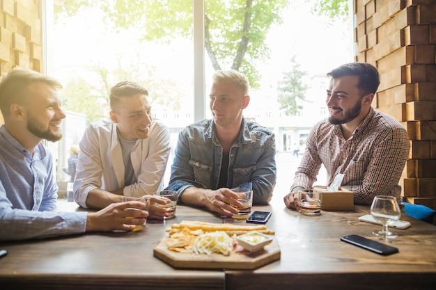 Männliche freunde, welche die getränke mit snack im restaurant genießen