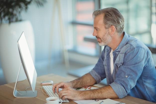 Männliche führungskraft, die am schreibtisch sitzt und am personalcomputer arbeitet