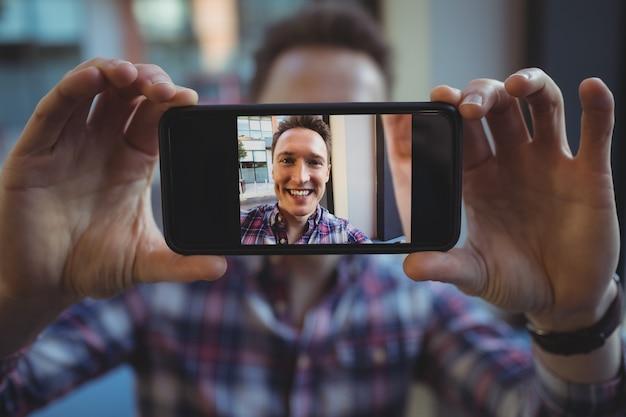 Männliche führungskraft, die selfie vom handy nimmt