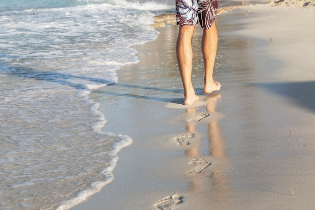 Männliche füße am ufer eines sandstrandes an einem sonnigen tag. junger mann geht am rand des wassers entlang und hinterlässt fußspuren. platz für text. tourismus und ruhe.