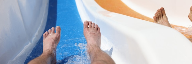 Männliche füße auf rutsche in einem wasserpark beim abstieg