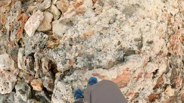Männliche füße gehen auf großen felsen und felsen. wandern sie in der felsigen gegend. ansicht von oben, 4k uhd.