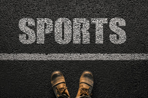 Männliche füße in schuhen stehen auf dem asphalt mit dem textsport, draufsicht. gesunder lebensstil und sportkonzept. ein schritt zur gesundheit kreativ