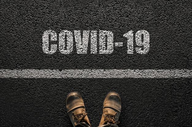 Männliche füße mit stiefeln auf dem asphalt mit dem text covid-19. humanitäts- und viruskonzept. coronavirus und reisen