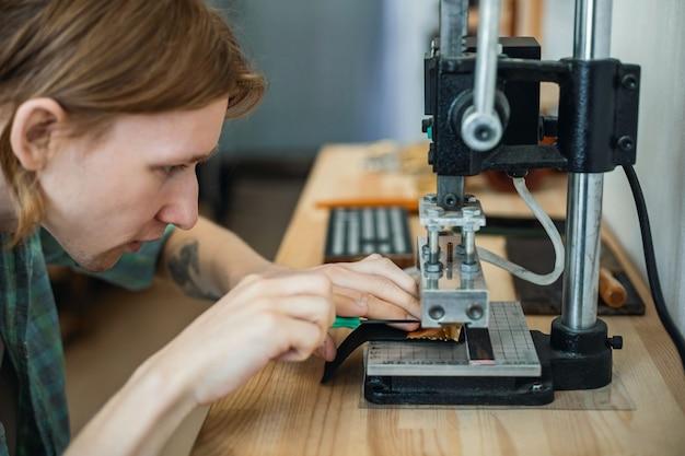 Männliche gerberstanzzeug verwendet ahle und maschinengerät, das in der lederwerkstatt handgefertigt wird