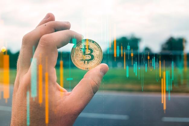 Männliche geschäftsmannhand, die eine bitcoin auf einem hintergrund des wachstumsdiagramms auf einem bildschirm des laptops hält. virtuelles geldkonzept und finanzwachstumskonzept auf diagrammhintergrund. trading mining von bitcoins.