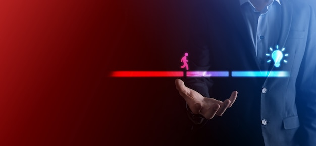 Männliche geschäftsmannhand hält einen verbindungsblock zwischen zwei brückenstraßen, damit ein silhouettenmann das ideensymbol gehen kann.