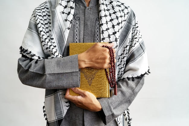 Männliche geste, die koran und gebetsperlen hält