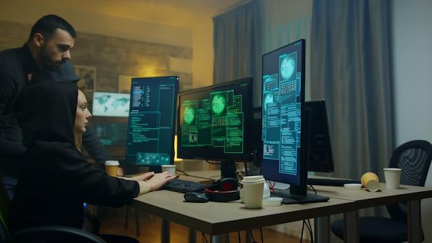 Männliche hacker, die sich ansehen, wie ihr cyberkriminelles mädchen daten vom covernment-server stiehlt.