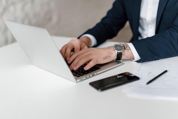 Männliche hände am arbeitsplatz mit laptop