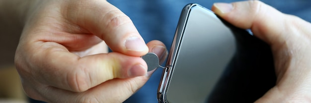 Männliche hände bekommen sim-kartensteckplatz seines smartphones aus nahaufnahme