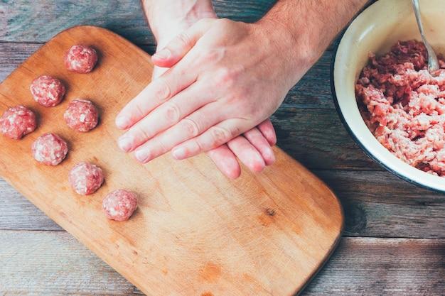 Männliche hände bereiten hausgemachte fleischbällchen-draufsicht-nahaufnahme vor