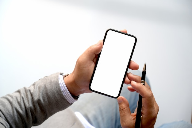 Männliche hände der draufsicht unter verwendung des smartphone an unscharfem hintergrund.