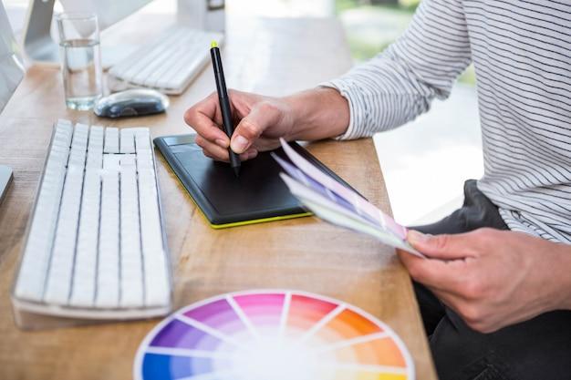 Männliche hände, die auf digitale tablette in einem hellen büro schreiben