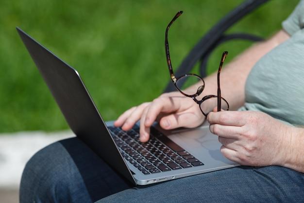 Männliche hände, die auf laptop im park tippen