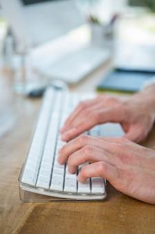 Männliche hände, die auf tastatur in einem hellen büro schreiben