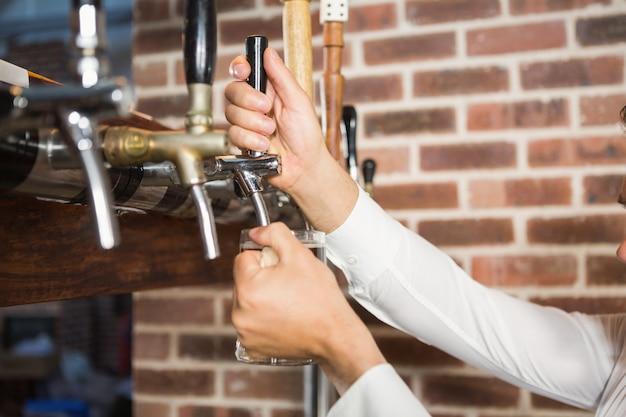 Männliche hände, die bier gießen