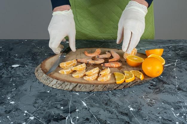 Männliche hände, die die garnelen und früchte auf marmortisch schneiden.