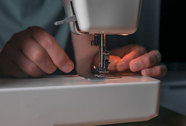 Männliche hände, die faden durch das stichloch in der nähmaschinenahaufnahme einführen