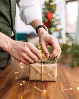 Männliche hände, die feiertagshandwerksgeschenkbox mit tannenzweig auf dem holztisch binden