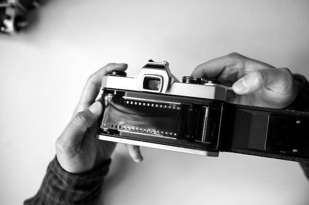 Männliche hände, die film retro kamera auf einem weißen tisch nachladen. horizontal