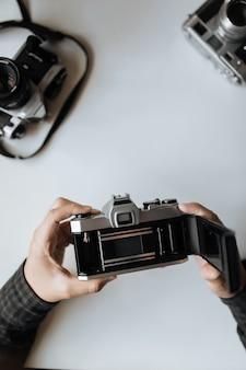 Männliche hände, die film retro kamera auf einem weißen tisch nachladen. vertikale