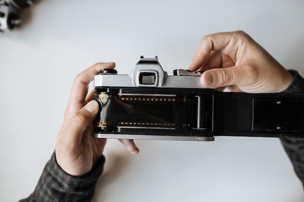 Männliche hände, die film retro kamera auf einem weißen tisch nachladen