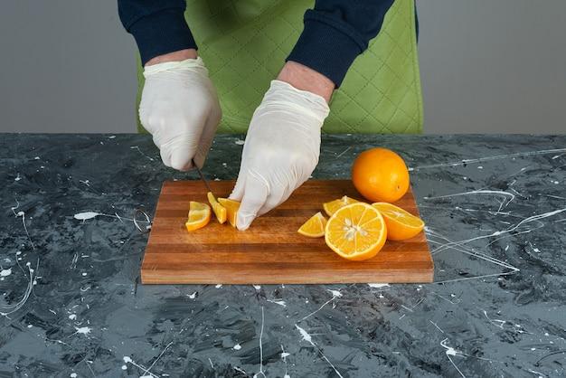 Männliche hände, die frische zitrone auf marmortisch schneiden.