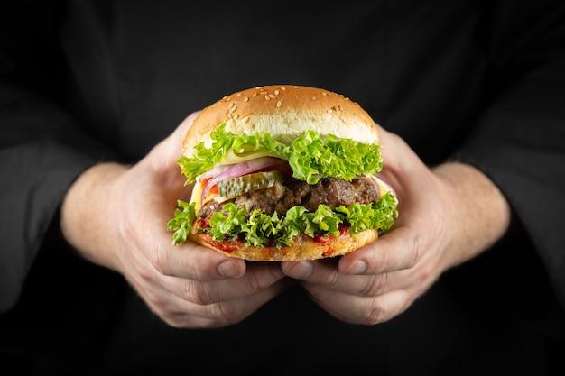 Männliche hände, die frischen köstlichen rindfleischburgermann in der schwarzen kochuniform halten
