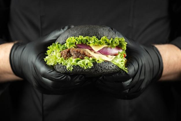 Männliche hände, die frischen köstlichen schwarzen rindfleischburgermann in der schwarzen kochuniform halten