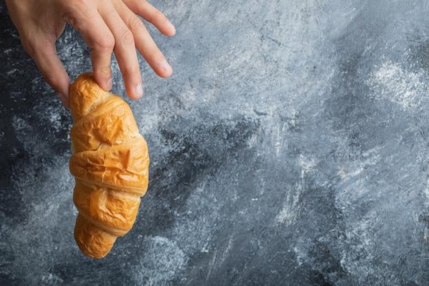 Männliche hände, die frisches croissant auf marmorhintergrund halten