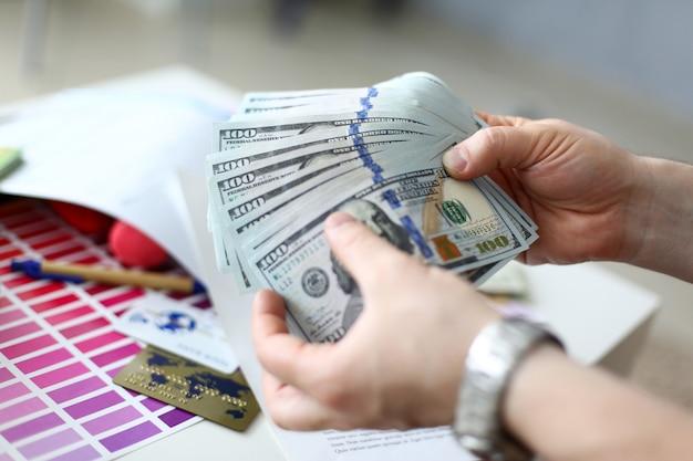 Männliche hände, die geld aus einer riesigen packung zählen