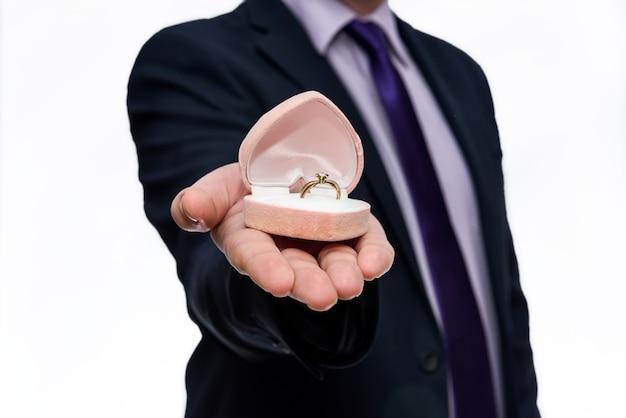 Männliche hände, die geschenkbox mit goldenem ring innen anbieten