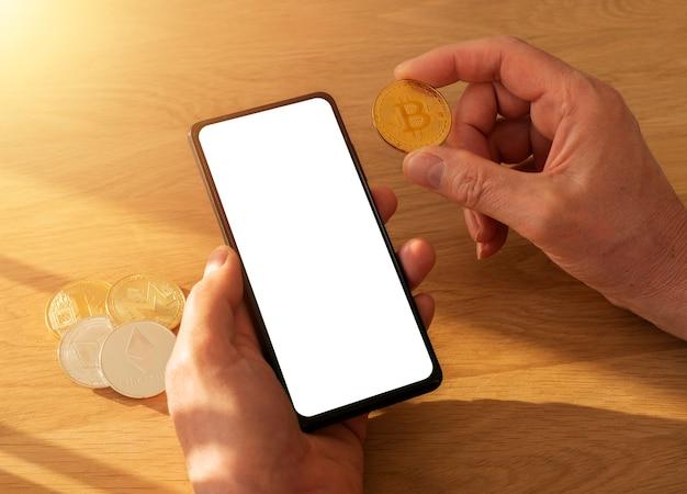 Männliche hände, die handy mit weißem leerem bildschirm für mockup und ethereum-münze in der hand über holztisch mit tageslicht halten