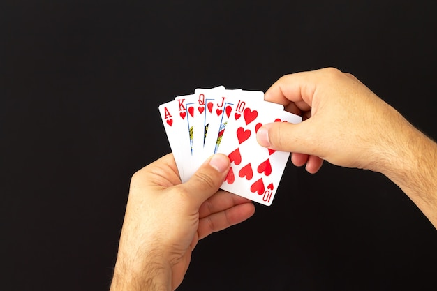 Männliche hände, die kombination der königlichen flush-pokerkarten auf dunklem hintergrund halten. casino, glück und glück konzept