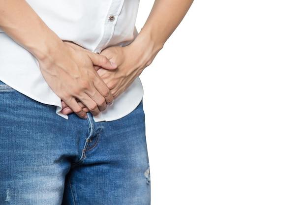 Männliche hände, die mittleren schritt der hose mit prostataentzündung halten