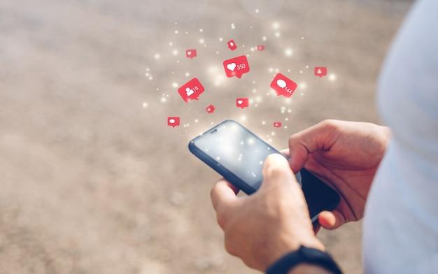 Männliche hände, die mobiles smartphone mit symbol social media und sozialem netzwerk verwenden. marketingkonzept.