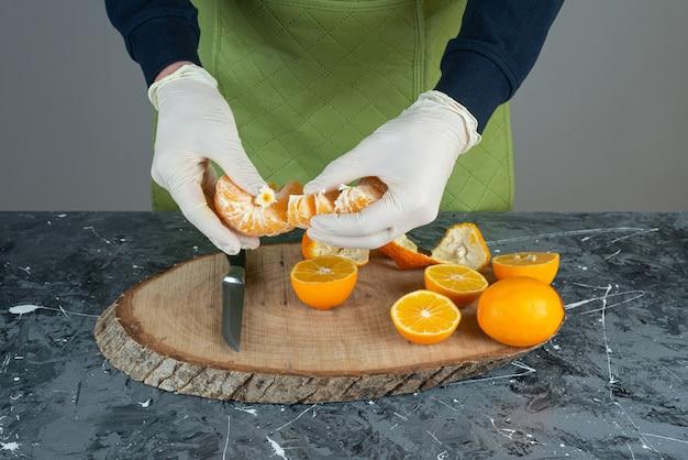 Männliche hände, die saftige mandarine auf marmortisch halten.