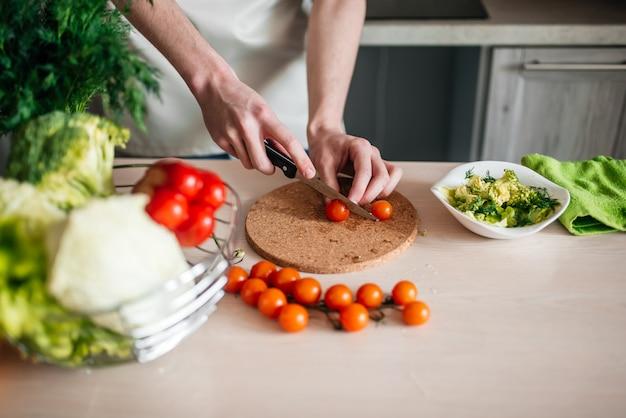 Männliche hände, die salat und zwiebel hacken und gesundes essen in der küche kochen.