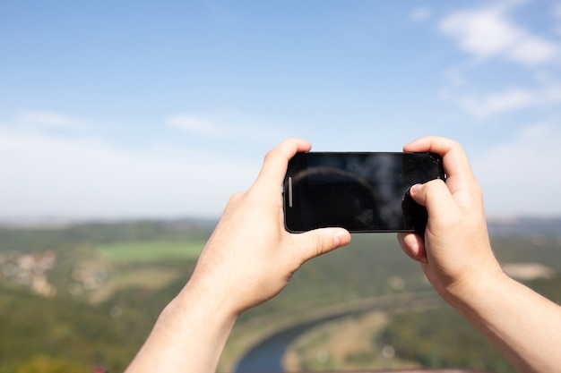 Männliche hände, die sein handy im freien halten und ein foto im landschaftspark machen