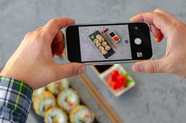 Männliche hände, die smartphone halten und ein foto von sushi-rolle auf grauem hintergrund machen