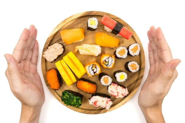 Männliche hände, die sushi zeigen, stellten auf hölzerne platte auf weißem hintergrund, japanisches lebensmittel ein.